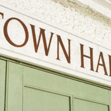 A sign above a traditional community town hall entrance.